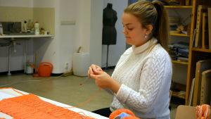 Elin Björkström sitter och stickar i ett klassrum. Framför henne ligger mängder av garn i olika orange nyanser.
