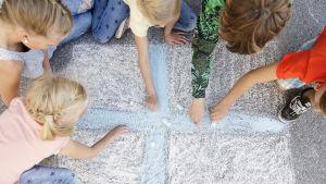 Barn ritar Finlands flagga med gatukritor