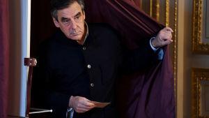 François Fillon stiger ut ur valbåset med en valsedel i handen den 27.11.2016