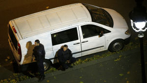 Poliser tar skydd bakom en paketbil i närheten av Bataclan.