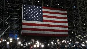Journalister väntar framför en stor USA-flagga.