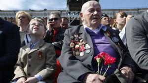 En krigsveteran och andra ryssar sitter på Röda torget den 9 maj 2015 i väntan på att segerdagsparaden ska inledas.