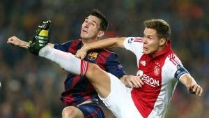 Lionel Messi och Niklas Moisander kämpar om bollen.