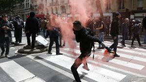 En maskerad demonstrant i Paris slänger tillbaka en tårgaskanister som polisen har avfyrat mot demonsranter