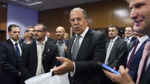 Sergej Lavrov bar in två flaskor vodka till journalisterna då de väntade på presskonferensen i Gèneve natten till lösdagen 10.9.2016