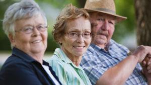 Tre äldre personer sitter bredvid varandra.
