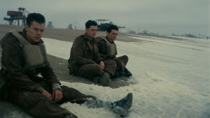 Soldaterna Alex (Harry Styles), Gibson (Aneurin Barnard) och Tommy (Fionn Whitehead) sitter på stranden i Dunkirk och låter vågorna skölja över dem.