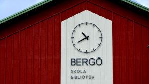 Bild av Bergö skolas yttervägg där det finns en stor klocka och texten Bergö skola bibliotek.