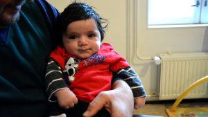Ett spädbarn sitter i en mans famn, barnet stirrar rakt in i kameran.