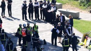 Theresa May omgiven av poliser vid olycksplatsen för höghusbranden.
