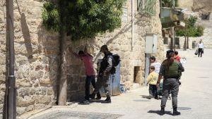 Israelisk soldat kroppsvisiterar palestinsk tonåring i Hebron på palestinska Västbanken
