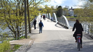 Cyklister och fotgängare påväg över en bro över älven i Umeå