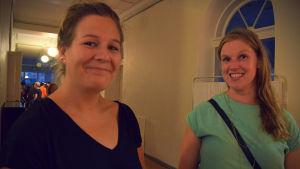 Två kvinnor tittar in i kameran och ler.