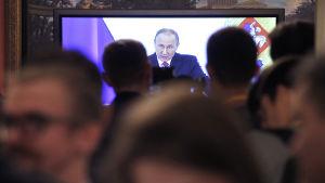 Journalister följer med Putins tal i palatset i Kreml i Moskva.