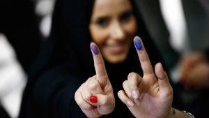 Iranska kvinnor visar bläcket på sina fingrar efter att de röstat i valet 26.2.2016