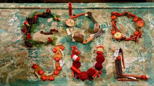 God jul hälsning i text av olika material på ett grönt bord