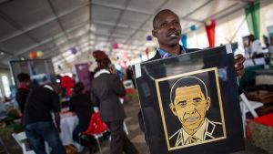 EN kenyansk man håller upp ett porträtt av Barack Obama.
