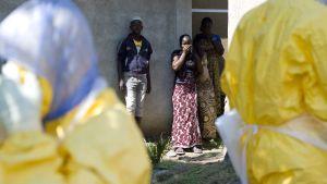 Grannar tittar på då guineanska röda kors-medarbetare för bort ett ebola-offer i november 2014