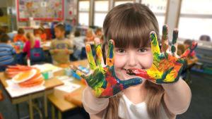 Flicka håller fram sina händer som har fingerfärg på.
