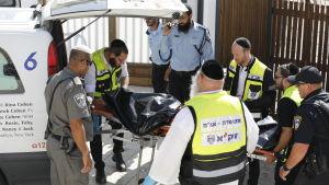 En av de palestinska gärningsmannen förs bort efter att han skjutits ihjäl nära Tempelberget i Jerusalem 14.7.2017