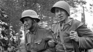 Två soldater går i armkrok, den ena gråter, den andra ser rakt in i kameran