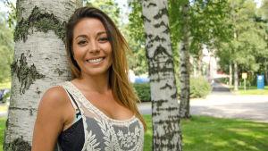 Realitystjärnan Amanda Harkimo lutar sig mot ett träd.