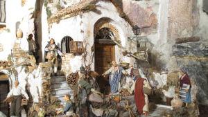 Keski-italialainen jouluseimi, jossa kylänäkymä valkoisine taloineen, kylänväkeä ja pyhä perhe.