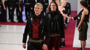Två män i folkdräkt av läder på röda mattan
