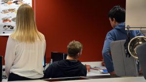 Tre ungdomar sitter med ryggen mot kameran vid en dator i en skola