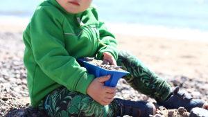 Barn leker i sanden.