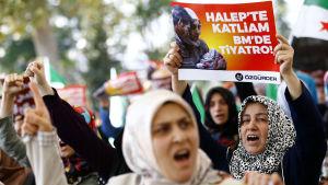 """Turkiska demonstranter i Istanbul protesterar mot de fortsatta ryska flygattackerna mot östra Aleppo. """"Massaker i Aleppo, Teater i FN"""", står de på skylten i bakgrunden"""