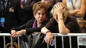 Oroliga demokrater väntar på valresultat vid ett staket.