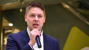 En medelåldedersman i vit skjorta och blå kavaj, han pratar med mikrofon i handen.