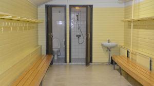 Ett omklädningsrum som är i ganska dåligt skick. Väggarna är citrongula och det finns träbänkar på sidorna.