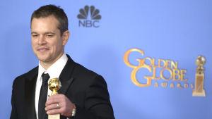 Skådespelaren Matt Damon håller i en Golden Globe-statyett.