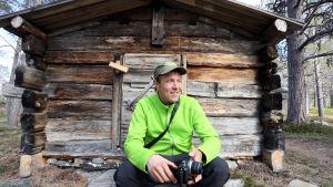 Mikko Peltola istuu vanhan aitan edessä Sevettijärvellä