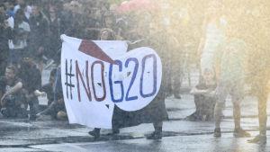 Demonstranter med en banner med texten #nog20