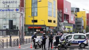 Poliser utanför ett köpcenter i Paris efter ett rånförsök i en affär den 13 juli 2015.