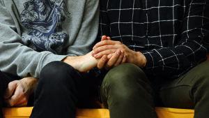 Två män som håller varandra i handen.