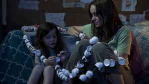 Brie Larson och Jacob Trembley sitter på golvet med ett hälsabadn av äggskal virat omkring sig.