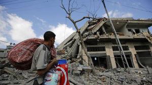 En palestinsk man bär sina saker efter att ha räddat dem från sitt söndebombade hem i östra Gaza City.