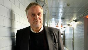 Antti Koski står i en korridor och ser rakt in i kameran.