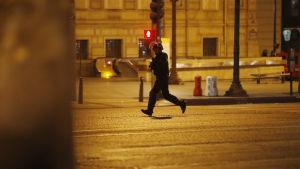 En polis springer på en folktom gata i Paris.