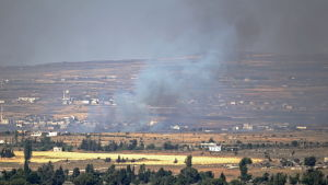Rök stiger upp från en syrisk efter stridigheter i staden Quneitra.