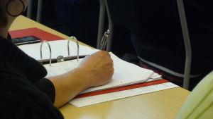 Studerande skriver på ett papper.