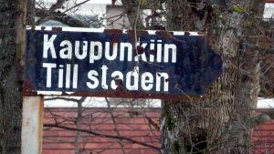 Gatuskylt med texten Kaupunkiin Till staden