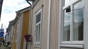 """Trähus med """"skvallerspegel"""" vid fönstret."""
