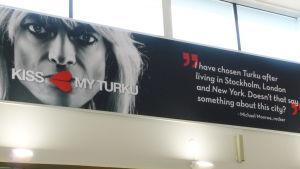 Kiss My Turku-reklam med Michael Monroe på Åbo flygplats.
