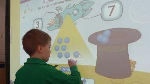 Espoon Olarin päiväkodin esikoululaiset tekevät älytaululla matematiikan tehtäviä.