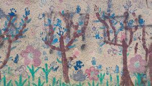 """Det stod """"Gasa araberna"""" på Shuhada Street Kindergartens vägg i Hebron. Så dagisbarnen målade över klottret med blommor."""